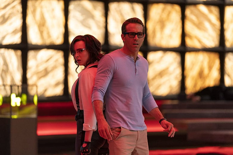 Jodi Comer and Ryan Reynolds stand back to back in a futuristic room in a still from Free Guy.