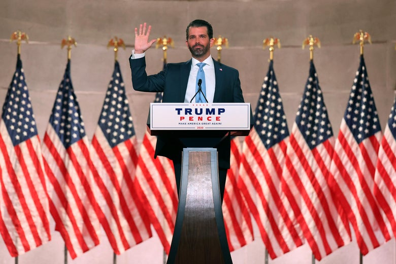 Donald Trump Jr. speaks in front of several American flags.