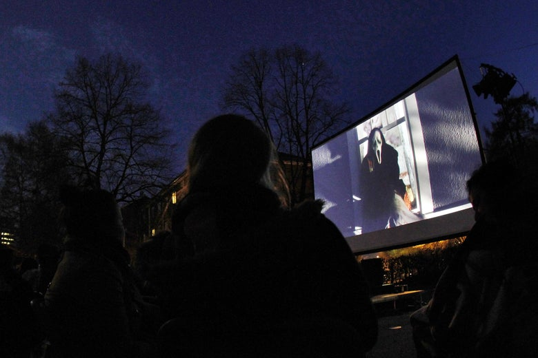 On an outdoor screen, ghostface from the Scream franchise appears. A crowd watches outside in the dark.