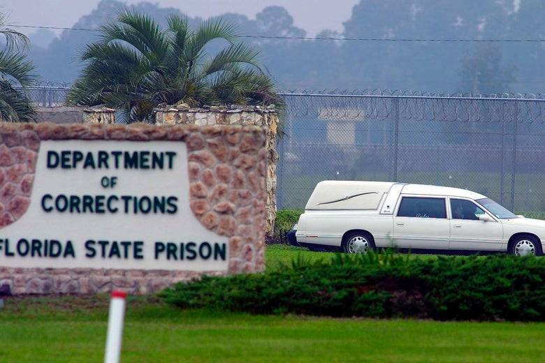 A white hearse drives by a sign for the Florida Department of Corrections