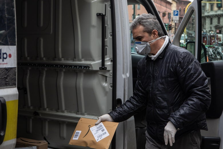 MILAN, ITALY - MARCH 11: A courier, wearing a respiratory mask, handles an Amazon parcel on March 11, 2020 in Milan, Italy. The Italian Government has strengthened up its quarantine rules, shutting all commercial activities except for pharmacies, food shops, gas stations, tobacco stores and news kiosks in a bid to stop the spread of the novel coronavirus. (Photo by Emanuele Cremaschi/Getty Images)