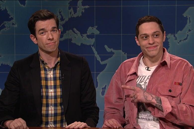 John Mulaney and Pete Davidson sitting behind the Weekend Update desk.