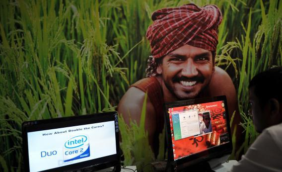 At an IT event in Karnataka, India, an attendee works on a computer in front of a poster of a farmer.