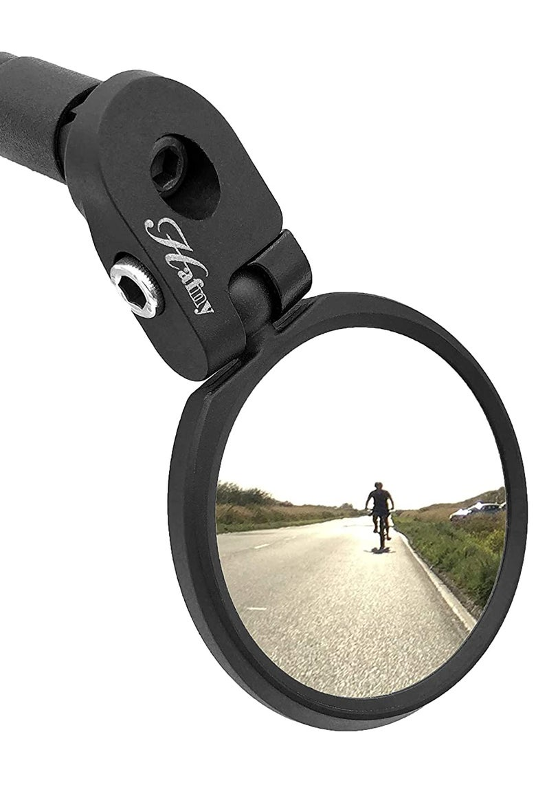 A bike mirror reflects a cyclist.