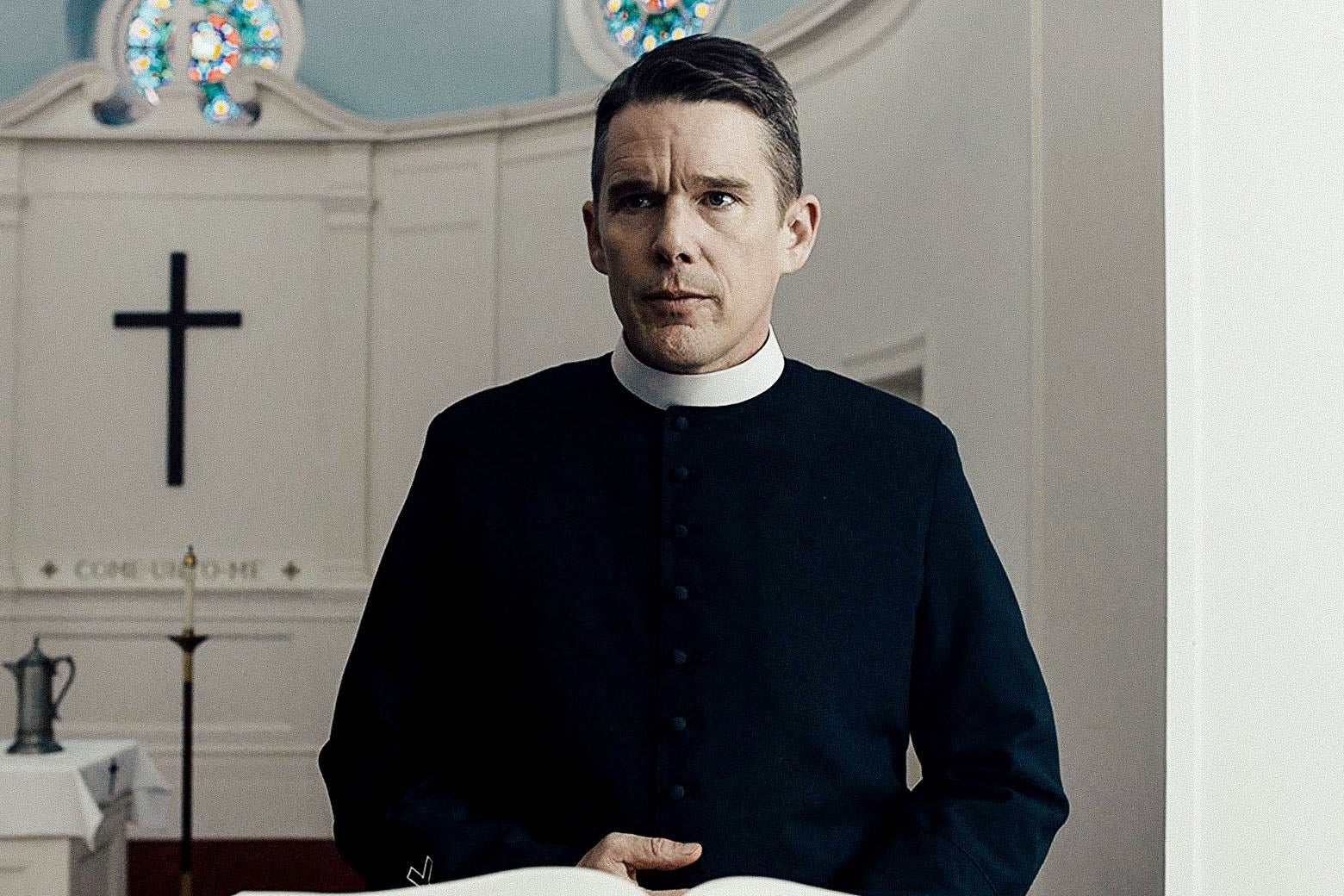 Ethan Hawke, dressed as a reverent at the front of a church, in the film First Reformed.