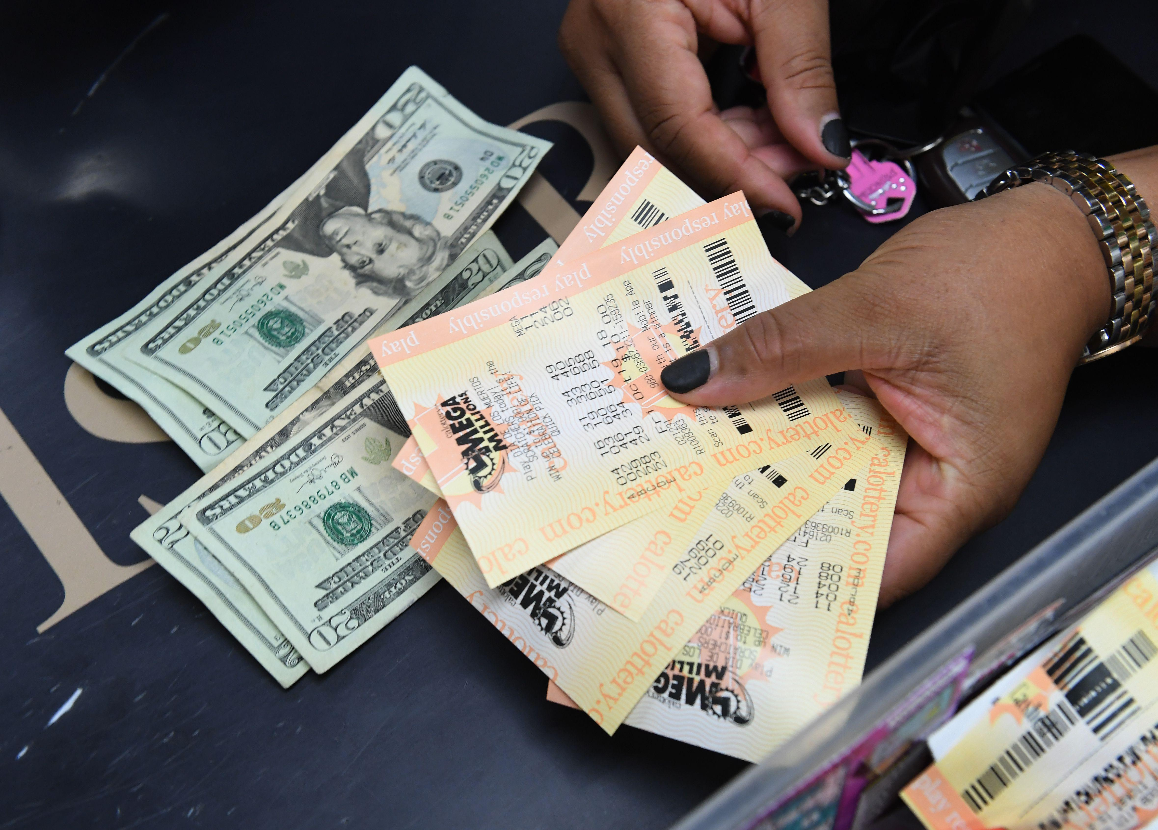 A woman's hand holds out four Mega Millions tickets. On the counter below her hand are a small stack of $20 bills.