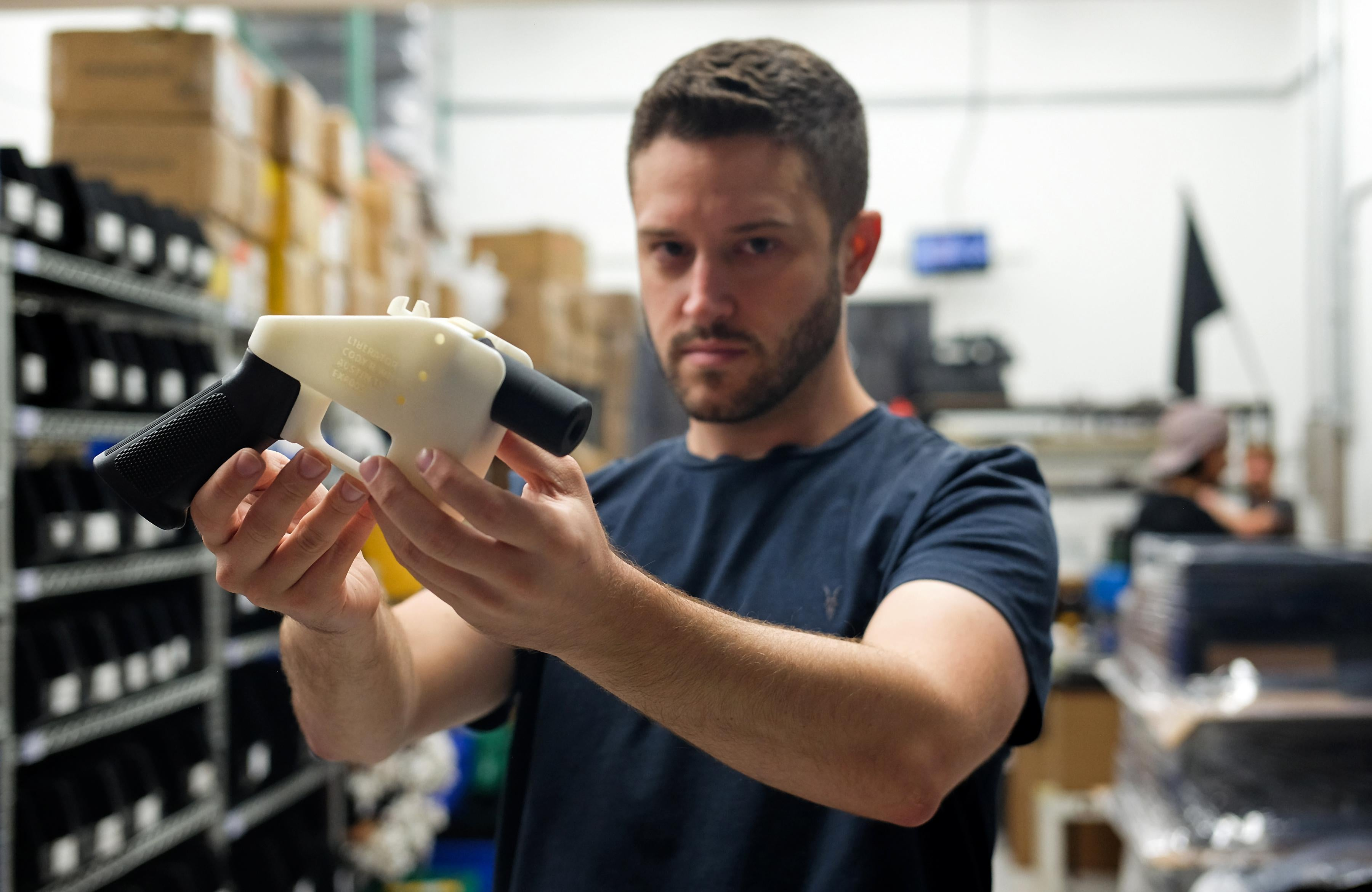 Cody Wilson holds up a black-and-white 3D-printed plastic gun while standing in his factory.