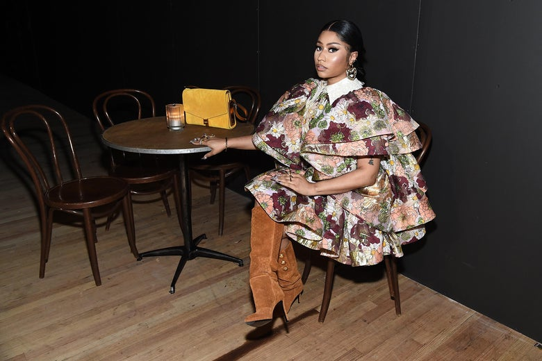 Nicki Minaj, in an elaborate dress and boots, sits at a table that holds a purse and a candle.