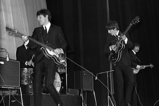The Beatles performing onstage.
