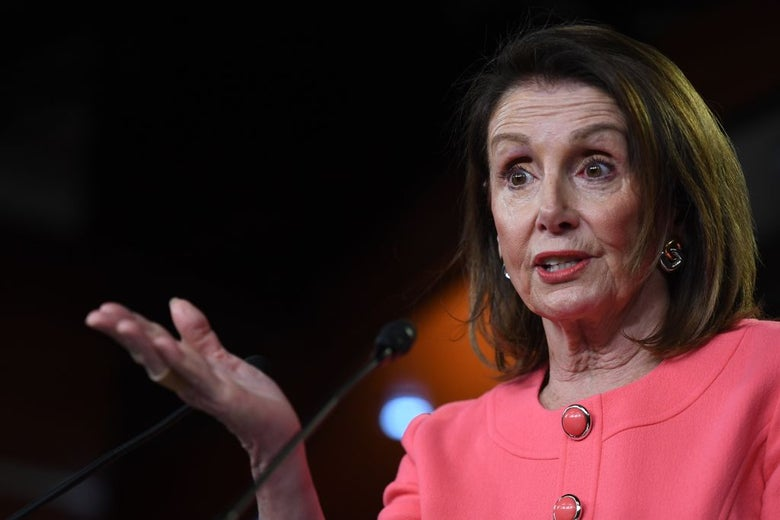 Pelosi gestures with her right hand while speaking into a microphone.