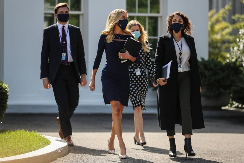 McEnany and three others walking and wearing masks
