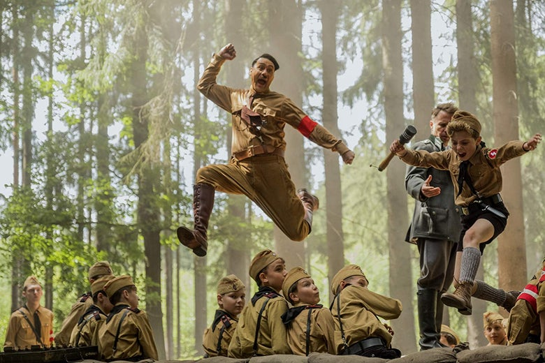 Taiki Waititi, in a still from Jojo Rabbit, leaps with joy, dressed as Hitler.