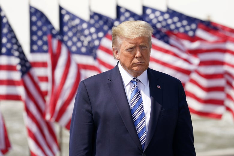 Trump standing in front of a bunch of American flags outside