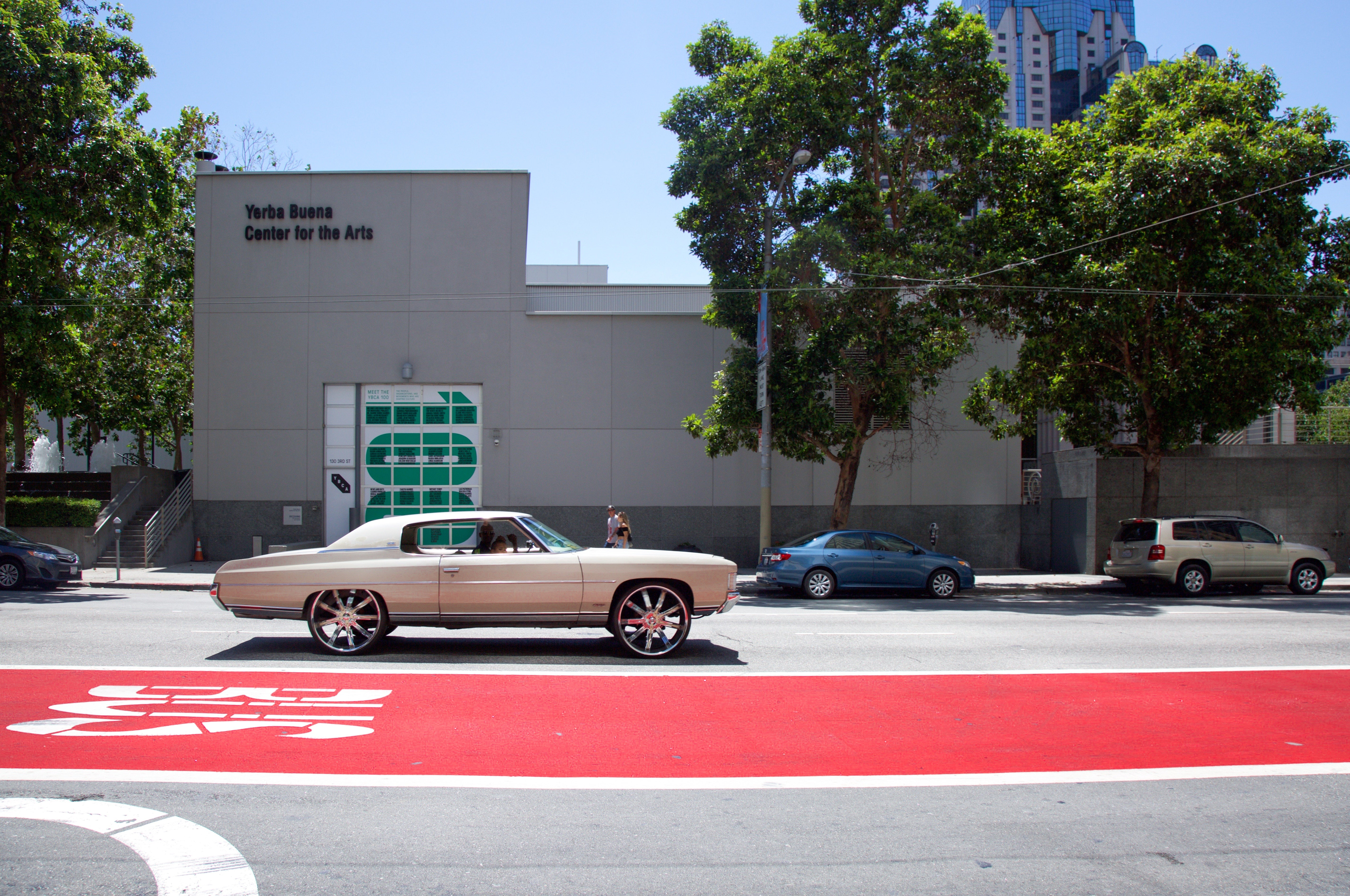 A white car and a red bus lane on a San Francisco street.
