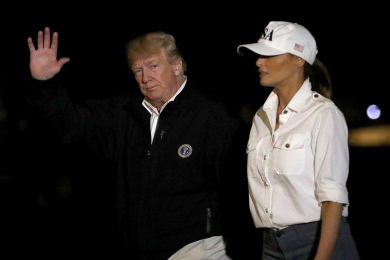 Trump, wearing a fleece, waves to the camera while Melania walks alongside him in a baseball cap.
