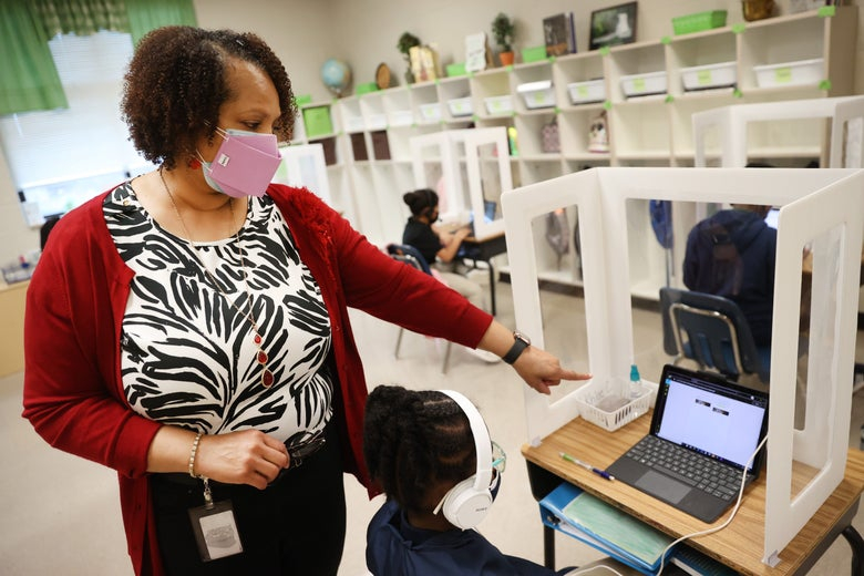 A masked teacher stands beside a student wearing headphones while working on a laptop inside her desk partition. The teacher points to the student's screen.