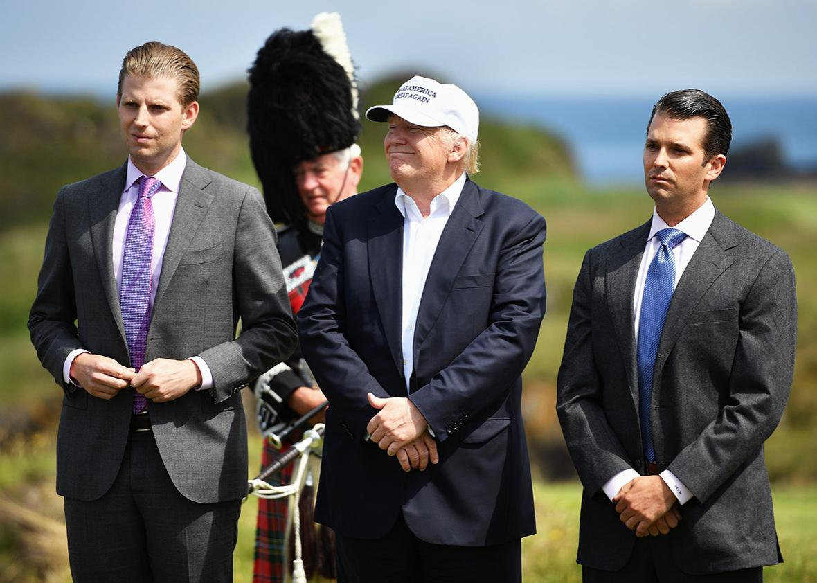 Presumptive Republican nominee for US president Donald Trump stands with his two sons Donald Trump Jr., Eric Trump,following a press conference on the 9th tee at his Trump Turnberry Resort on June 24, 2016 in Ayr, Scotland.