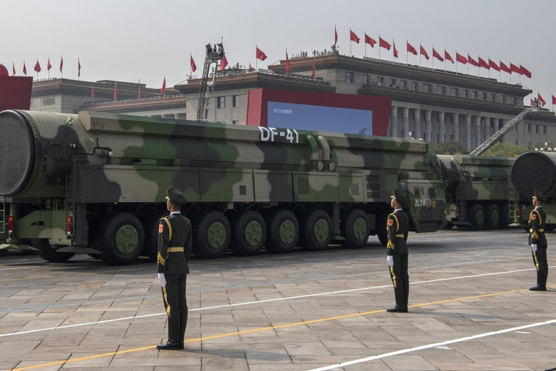 Chinese military personnel stand at attention in front of a convoy of huge missiles