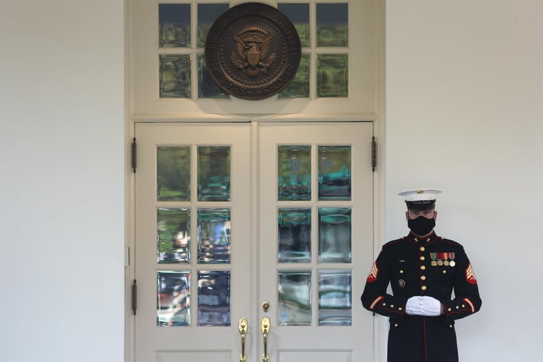 A masked U.S. Marine stands guard outside the West Wing of the White House on Friday