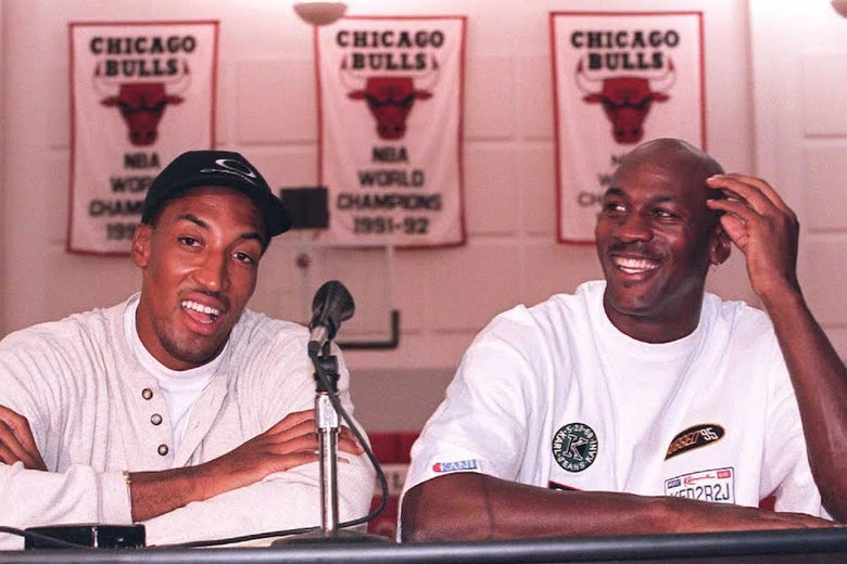 Scottie Pippen and Michael Jordan sitting at a table with a microphone, and behind them are banners for three Bulls championships.