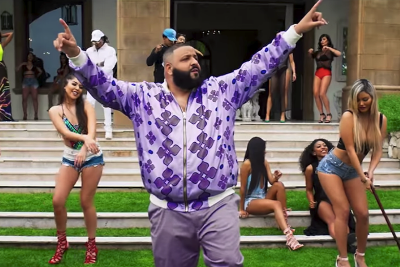 DJ Khaled points both index fingers in the air as scantily clad women dance behind him.