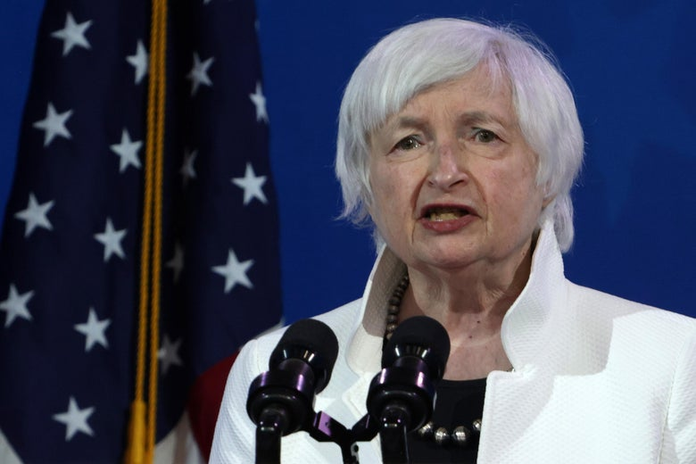 Janet Yellen speaks into a pair of microphones while standing in front of a U.S. flag.
