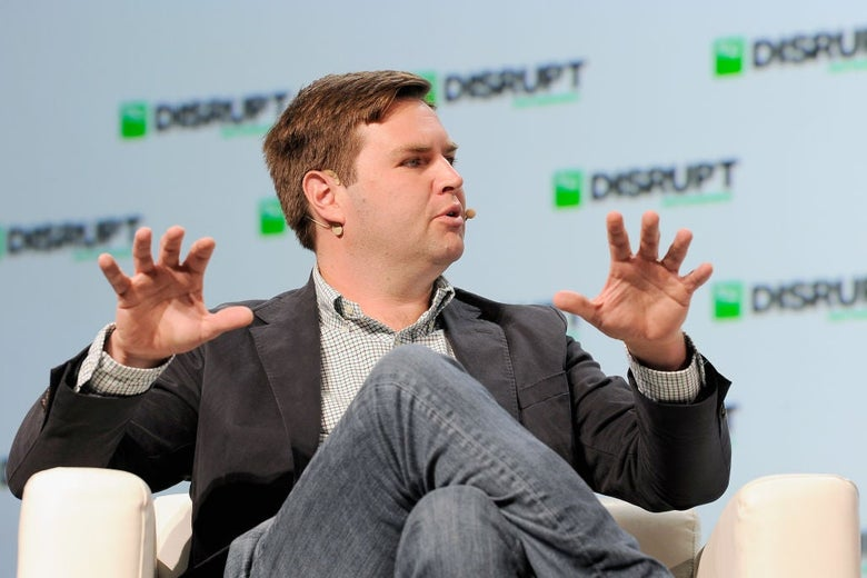 J.D. Vance, wearing a sport coat and a wireless headset, gestures while seated in a plush chair at a tech conference.