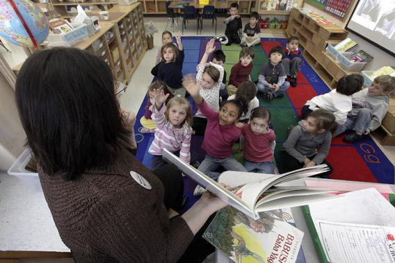 Students in Connie Levin's kindergarten class raise their hands to answer questions during story time.