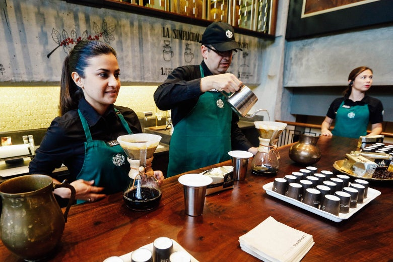 Workers prepare coffee during the inauguration of the first Starbucks in Bogota, Colombia on July 16, 2014.