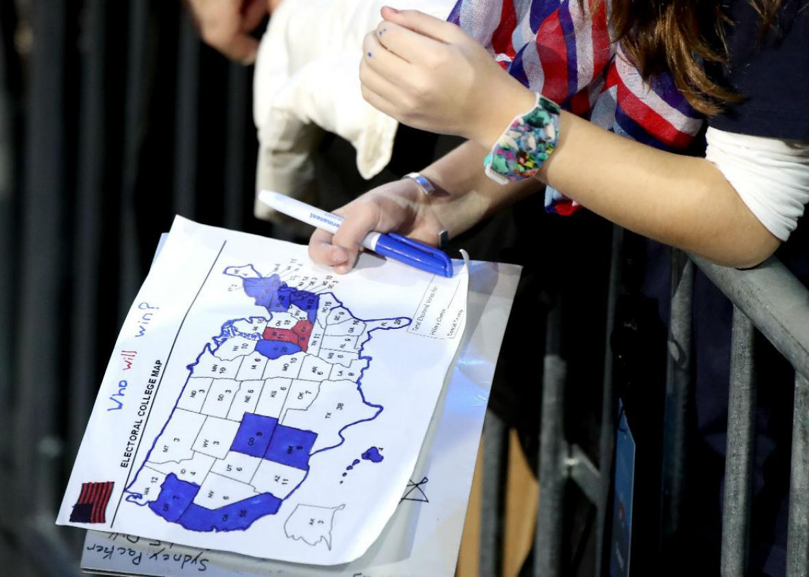 A woman holding a partially filled-in electoral map from the 2016 election.