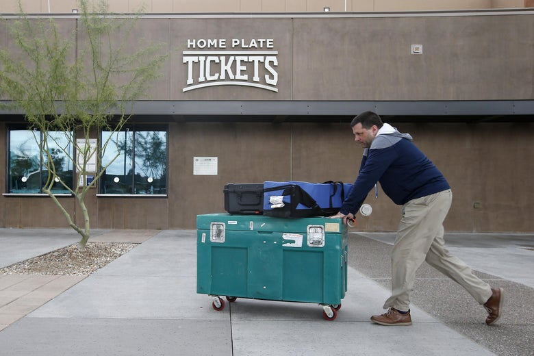 Stadium personnel move equipment past the ticket windows at American Family Fields stadium, spring training home of the Milwaukee Brewers, following Major League Baseball's decision to suspend all spring training games on March 12, 2020 in Phoenix, Arizona.