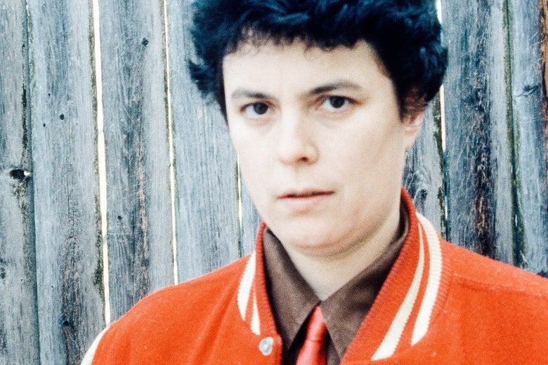 A young woman with short hair, a letter jacket, and a red tie, stares confidently into the camera.
