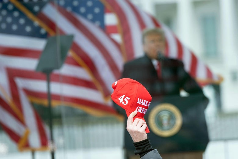 """A person raises a """"Make America Great"""" hat as US President Donald Trump speaks to supporters from The Ellipse near the White House on January 6, 2021, in Washington, DC."""