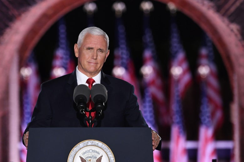 Mike Pence stands at a podium, with American flags behind him