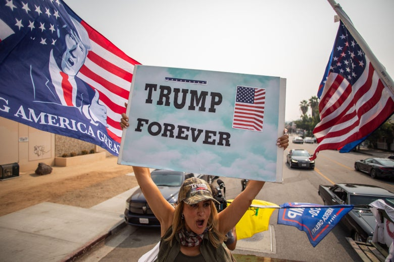 """A woman brandishes a """"Trump Forever"""" sign from the back of a military truck."""
