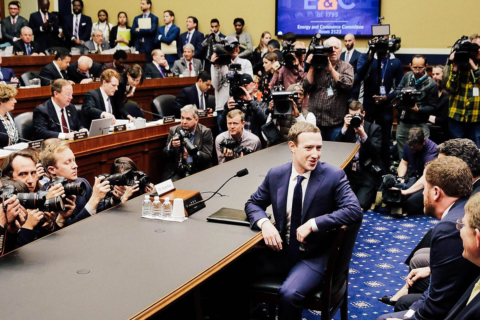 Mark Zuckerberg turns to talk to colleagues at a hearing.