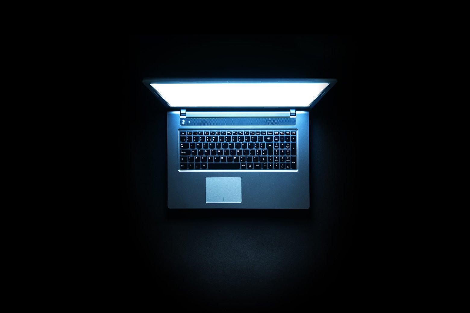 A laptop glowing in a dark room.