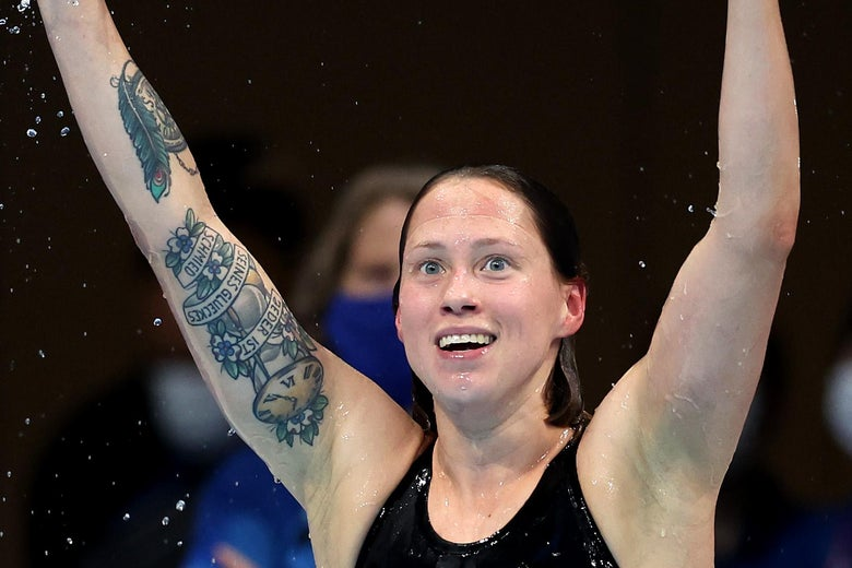 Kohler smiling with her arms raised in her swimsuit, a large tattoo described below visible on her right arm