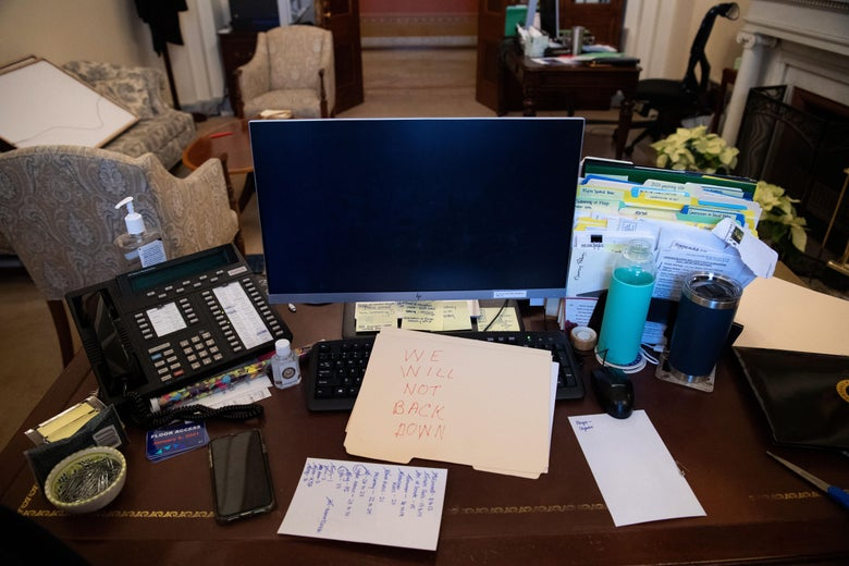 "A desk in Pelosi's office with papers, a phone, and a computer on it. A manila folder with ""WE WILL NOT BACK DOWN"" written on it in red has been placed over the keyboard."