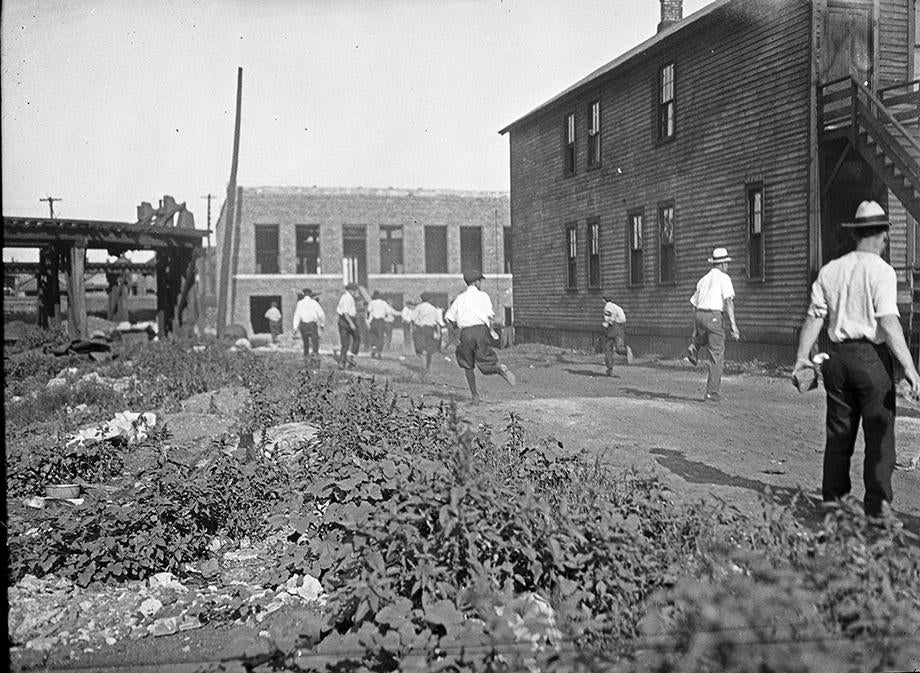 Members of a white mob run with bricks in hand, during the Chicago race riot of July and August, 1919.