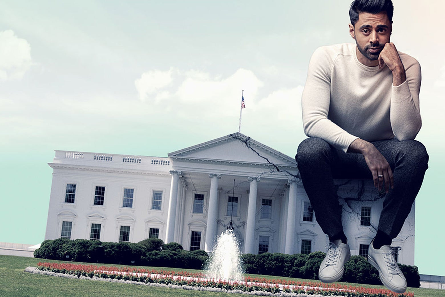 In this photo illustration, Hasan Minhaj sits on one corner of the White House. He's very large, and the White House is very small and seat-size.