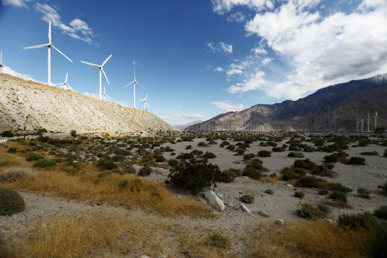 Wind turbines rotate at a wind farm in on a hill in California