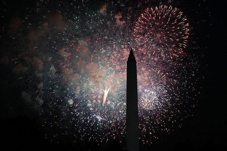 Fireworks explode behind the Washington Monument.
