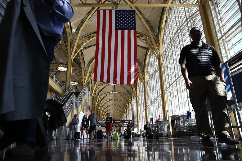 Travelers walk to their gates in the concourse of Reagan National Airport in Washington.