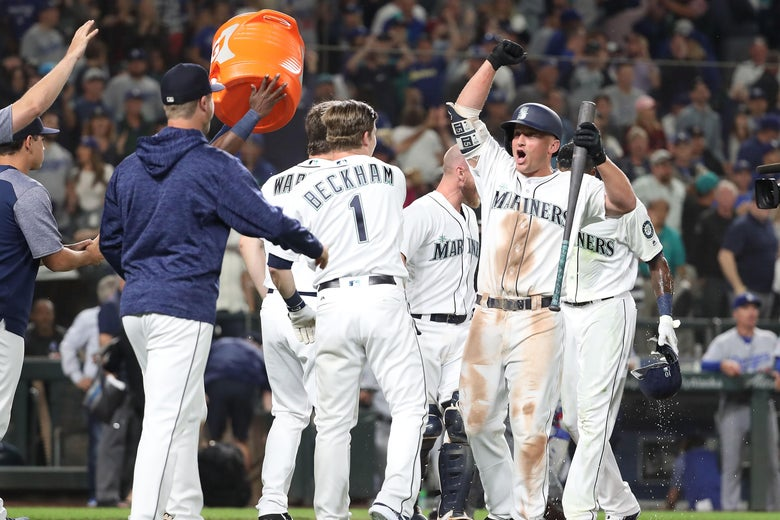 SEATTLE, WA - AUGUST 18:  Kyle Seager #15 of the Seattle Mariners (R) celebrates with teammates after a balk by Dylan Floro #51 of the Los Angeles Dodgers in the tenth inning to win the game 5-4 during their game at Safeco Field on August 18, 2018 in Seattle, Washington.  (Photo by Abbie Parr/Getty Images)