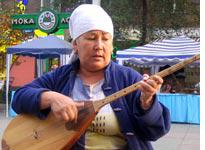 A Kazakh woman plays the dombra, a traditional instrument. Click image to expand.