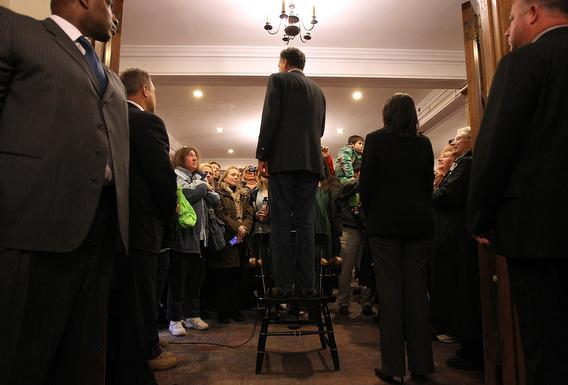 Mitt Romney stands on a chair as he speaks to an overflow crowd during a spaghetti dinner at Tilton School on January 6, 2012 in Tilton, New Hampshire