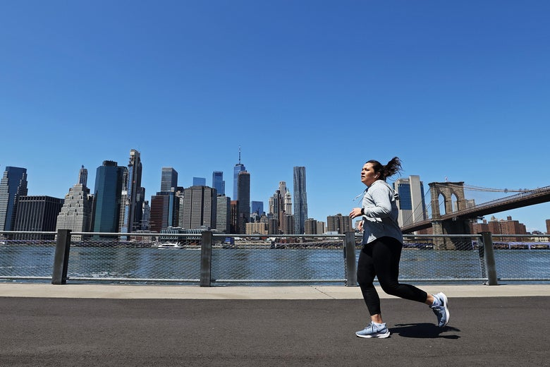 A woman running near the Manhattan skyline, on an uncrowded sidewalk