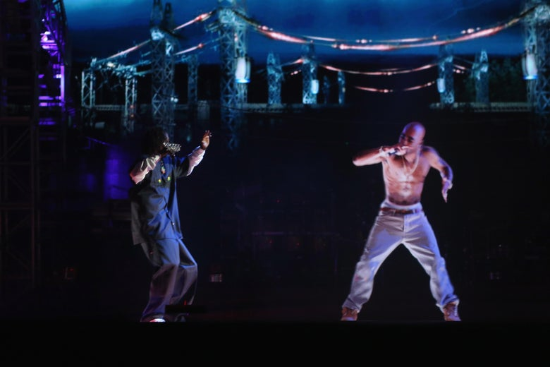 Tupac's hologram rapping into a holographic microphone as Snoop hypes him up on a dark stage