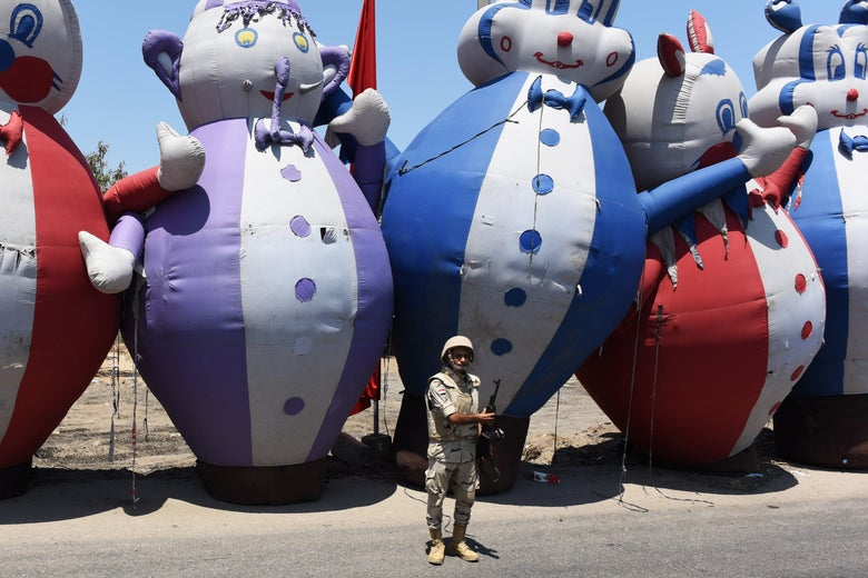 A lone Egyptian soldier holds a gun and stands in front of five towering clown floats on the banks of the Suez Canal